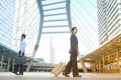 Uomo d'affari che tira valigia che cammina nella città moderna, concetto di affari Immagini Stock