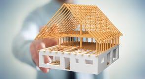 Uomo d'affari che tocca 3D che rende la casa non finita di piano con il suo Fotografia Stock