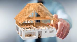 Uomo d'affari che tocca 3D che rende la casa non finita di piano con il suo Fotografia Stock Libera da Diritti