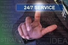 Uomo d'affari che tocca il bottone di servizio 24-7 sullo schermo virtuale Fotografia Stock Libera da Diritti