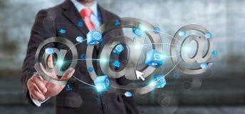 Uomo d'affari che tocca l'icona del email della rappresentazione 3D con il suo dito Immagini Stock