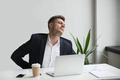 Uomo d'affari che tocca mal di schiena posteriore facente male di sensibilità dopo sedentar Immagini Stock