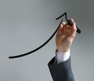 Uomo d'affari che traccia un diagramma di uptrend Immagini Stock