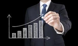 Uomo d'affari che traccia un grafico crescente Immagine Stock