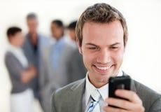 Uomo d'affari che trasmette un testo davanti alla sua squadra Fotografia Stock Libera da Diritti