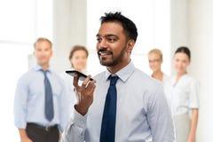Uomo d'affari che usando comando di voce sullo smartphone fotografia stock