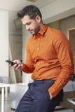 Uomo d'affari che usando il suoi telefono cellulare e invio di messaggi di testo mentre sedendosi alla scrivania immagini stock libere da diritti