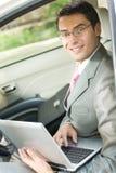 Uomo d'affari che utilizza computer portatile nell'automobile Immagine Stock Libera da Diritti