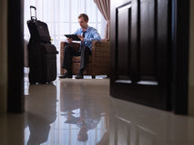Uomo d'affari che utilizza il pc digitale del ridurre in pani nella camera di albergo Immagini Stock