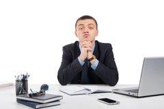 Uomo d'affari che vi esamina scettico che vi sedete al suo scrittorio immagine stock libera da diritti