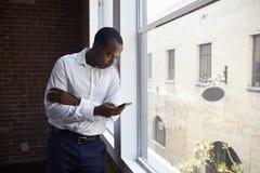 Uomo d'affari Checking Phone Standing dalla finestra dell'ufficio immagini stock libere da diritti