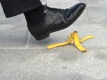 Uomo d'affari circa al punto su una pelle di banana Fotografia Stock