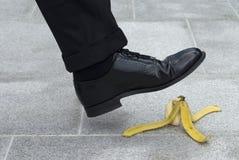 Uomo d'affari circa al punto su una pelle di banana Fotografie Stock Libere da Diritti
