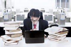 Uomo d'affari circondato con i libri ed il calcolatore Fotografia Stock Libera da Diritti