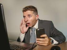 Uomo d'affari colpito e sorpreso in vestito e legame che lavora allo scrittorio del computer portatile dell'ufficio che ritengono fotografie stock libere da diritti