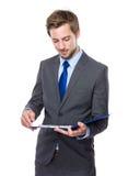 Uomo d'affari colto sulla lavagna per appunti immagine stock