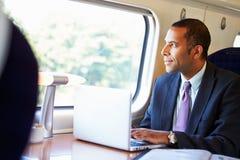 Uomo d'affari Commuting To Work sul treno e sul computer portatile usando Fotografie Stock