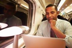 Uomo d'affari Commuting To Work sul treno e sul computer portatile usando Immagini Stock