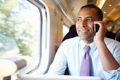 Uomo d'affari Commuting To Work sul treno facendo uso del telefono cellulare immagine stock