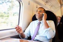 Uomo d'affari Commuting To Work sul treno facendo uso del telefono cellulare fotografie stock libere da diritti