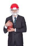 Uomo d'affari competitivo che gioca football americano Immagini Stock