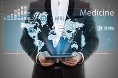 Uomo d'affari in compressa nera della tenuta della mano del vestito Infographics medico sullo schermo virtuale vuoto del fondo gr immagini stock