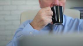 Uomo d'affari in computer portatile di uso della stanza dell'ufficio e bere un caffè archivi video