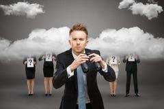 Uomo d'affari con binoculare contro il cielo tempestoso fotografia stock