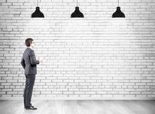 Uomo d'affari con caffè e un muro di mattoni Immagine Stock