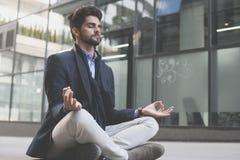 Uomo d'affari con gli occhi chiusi che praticano yoga fotografia stock libera da diritti