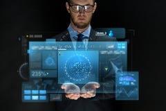 Uomo d'affari con gli schermi virtuali sopra il nero Fotografia Stock