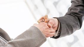 Uomo d'affari con handshake dei soldi con il partner immagini stock libere da diritti