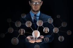 Uomo d'affari con i contatti della rete sopra il nero Immagini Stock