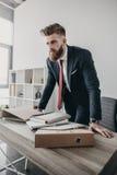Uomo d'affari con i documenti e le cartelle che stanno alla tavola in ufficio Fotografie Stock