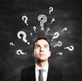 Uomo d'affari con i punti interrogativi Fotografia Stock
