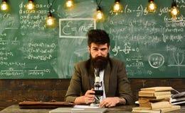 Uomo d'affari con i vetri e lo strumento ottico allo scrittorio Lavoro barbuto dell'uomo con il microscopio Uomo con la barba ed  Fotografie Stock Libere da Diritti
