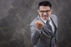 Uomo d'affari con il braccio su su fondo concreto grigio Fotografia Stock