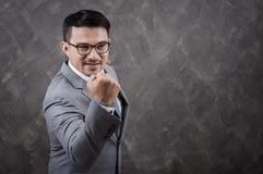 Uomo d'affari con il braccio su su fondo grigio Fotografia Stock