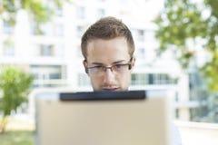 Uomo d'affari con il calcolatore del ridurre in pani in sosta Immagine Stock