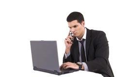 Uomo d'affari con il calcolatore superiore ed il telefono di giro Fotografia Stock Libera da Diritti