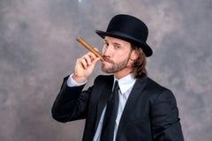 Uomo d'affari con il cappello di giocatore di bocce in vestito nero che fuma grande sigaro Fotografia Stock