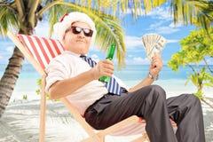 Uomo d'affari con il cappello di Santa che si siede sulla sedia e che tiene i dollari Immagini Stock Libere da Diritti