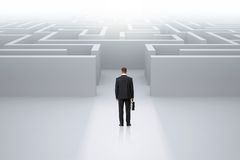 Uomo d'affari con il caso che sta davanti al labirinto Immagine Stock Libera da Diritti