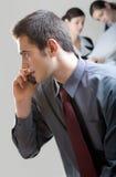 Uomo d'affari con il cellulare e due donne di affari su priorità bassa Fotografia Stock