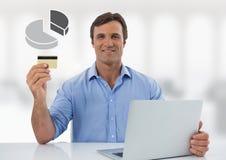 Uomo d'affari con il computer portatile allo scrittorio con il diagramma a torta e la carta assegni del diagramma Fotografie Stock