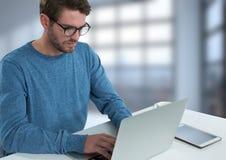 Uomo d'affari con il computer portatile allo scrittorio con fondo luminoso Immagini Stock