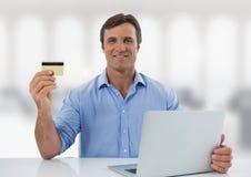 Uomo d'affari con il computer portatile allo scrittorio con fondo luminoso Fotografia Stock