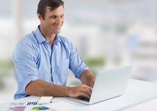 Uomo d'affari con il computer portatile allo scrittorio con fondo luminoso Fotografie Stock