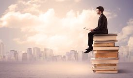 Uomo d'affari con il computer portatile che si siede sui libri Immagini Stock Libere da Diritti