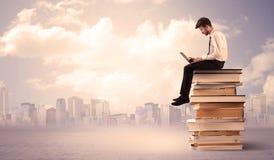 Uomo d'affari con il computer portatile che si siede sui libri Fotografie Stock Libere da Diritti